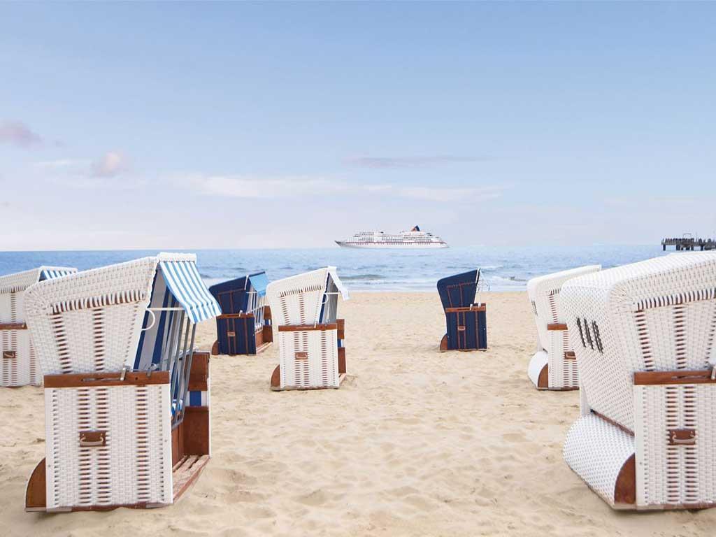 Strandkörbe an der Ostsee mit MS EUROPA im Hintergrund