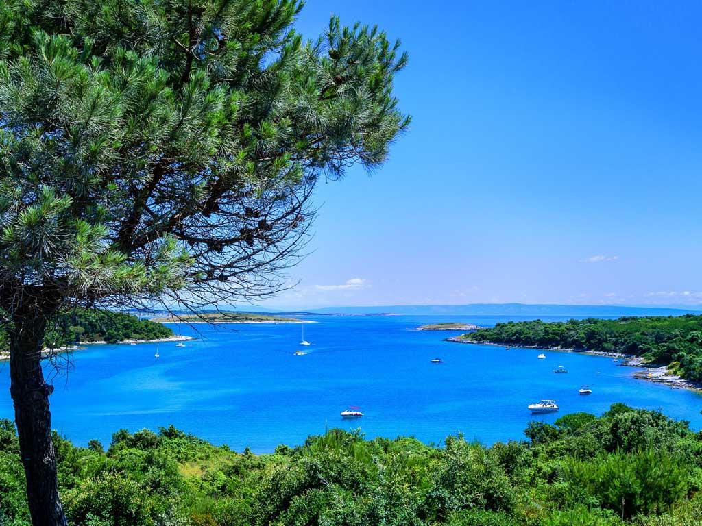 Himmelblaue Bucht mit grüner Landschaft