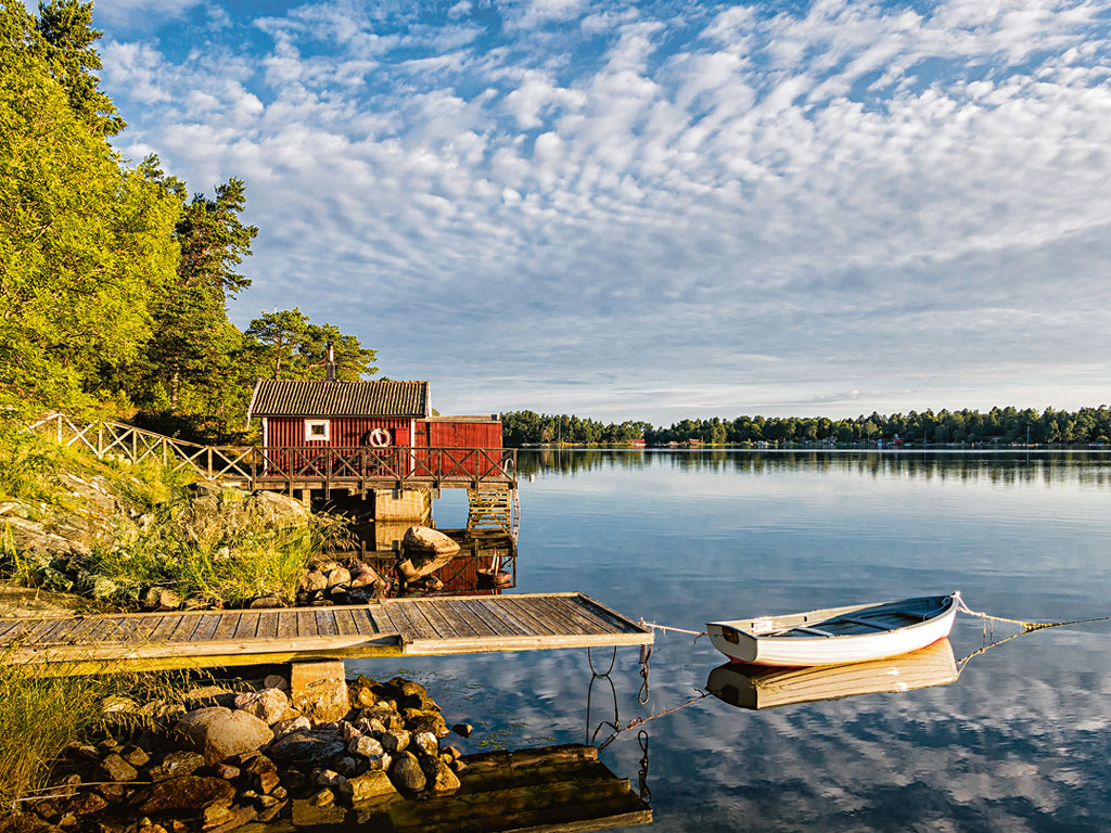 Kleiner Steg mit Boot und Haus